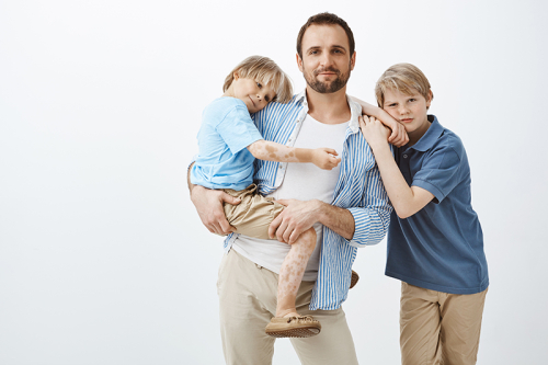 Single-father-with-two-cute-kids-standing-dad-holding-little-son-in-hands-and-smiling-broadly-while-older-brother-leaning-on-shoulder
